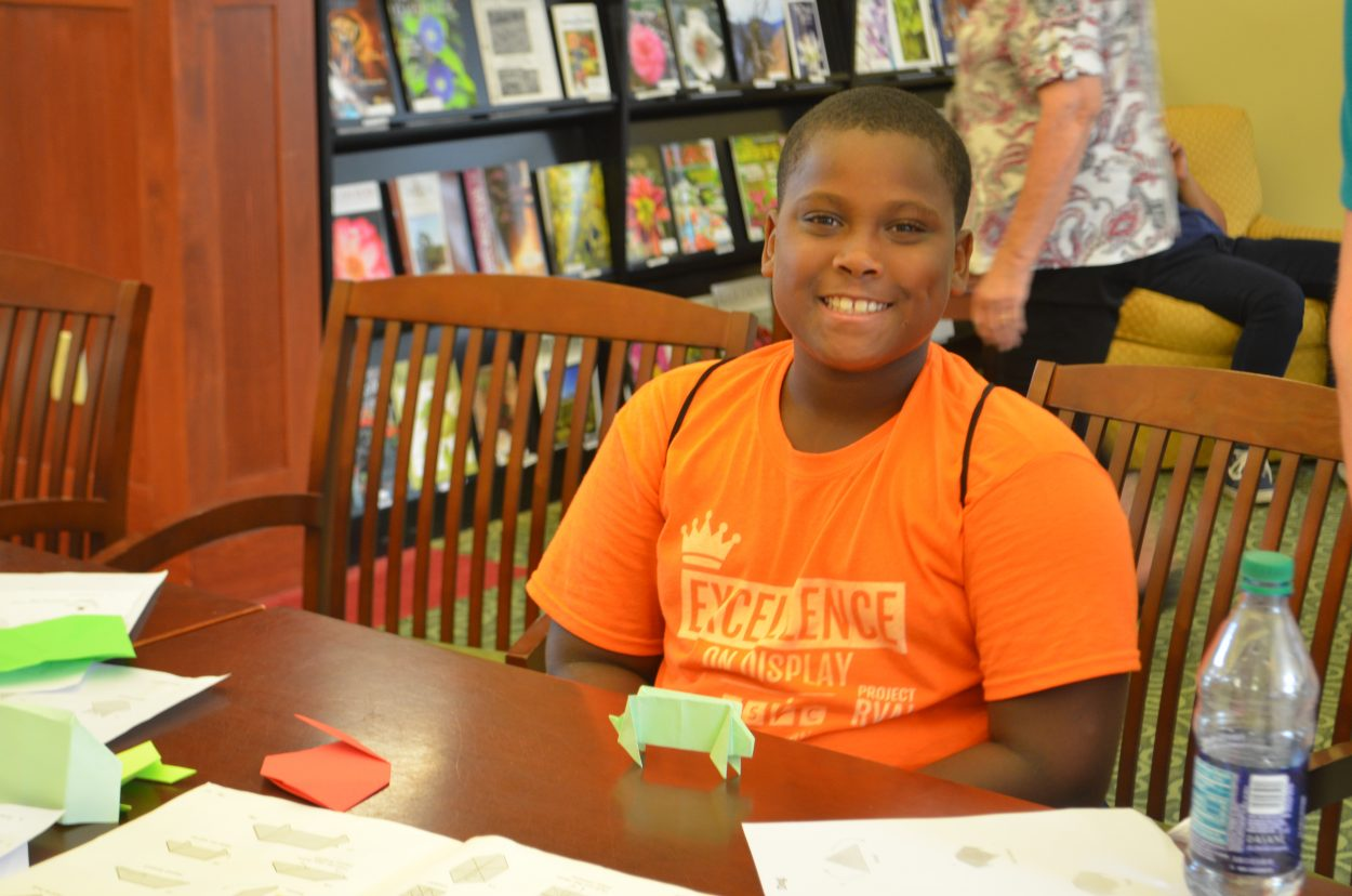 Image of a smiling boy in an orange T-shirt sitting at a table in a library. In front of him on the table is an origami pig folded from green paper.