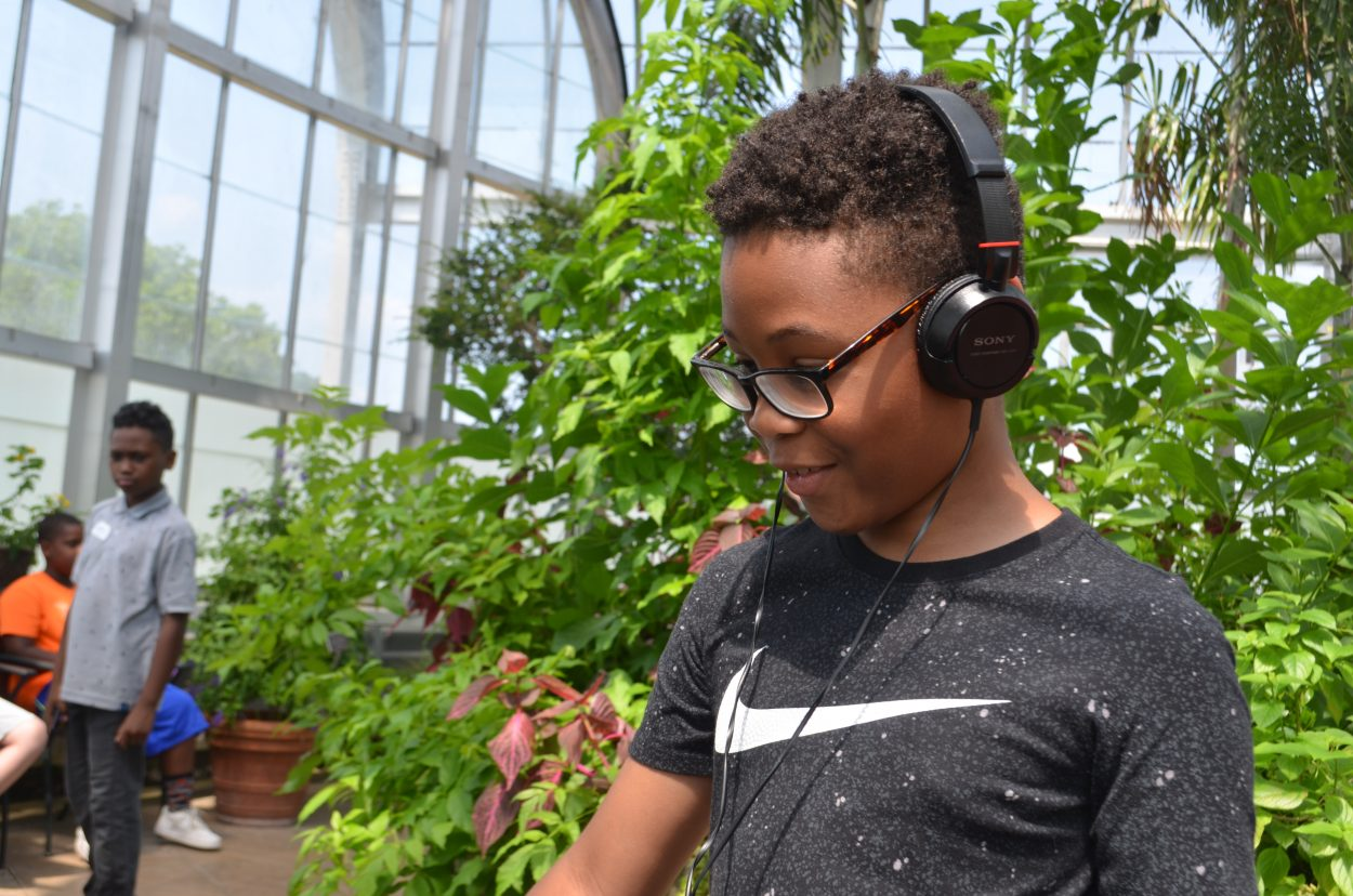 Image of a boy wearing glasses, a black T-shirt, and headphones standing in front of a large growth of plants. He looks away from the camera towards something out of the frame.