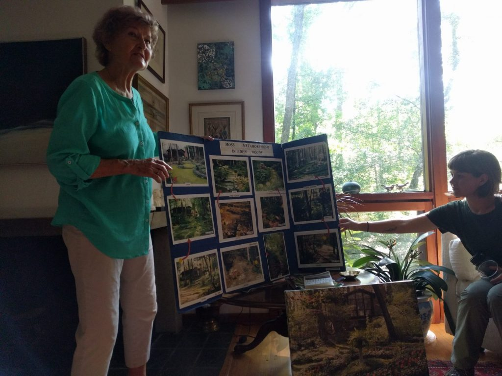 Image of two women holding up a blue tri-fold with various before and after pictures of a garden. The woman on the left, Norie Burnet, is blond with a teal long-sleeved shirt and white pants, and stands looking out into an unseen audience. The woman on the right, a Lewis Ginter Botanical Garden volunteer, has short cropped hair, a green T-shirt, and gardening pants, and holds the other side of the tri-fold while sitting down.