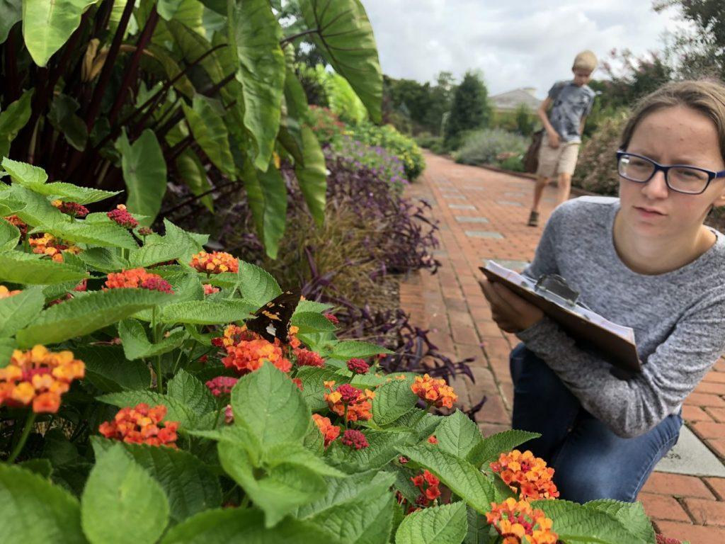 Citizen Scientist student takes notes in a garden.