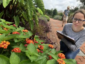 Student takes notes in a garden.
