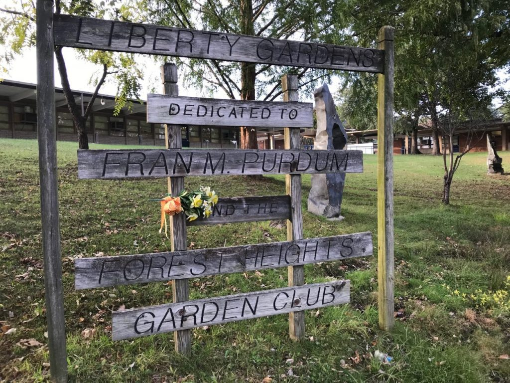 "A sign stating ""Liberty Gardens, Dedicated to Fran M. Purdum and the Forest Heights Garden Club"""