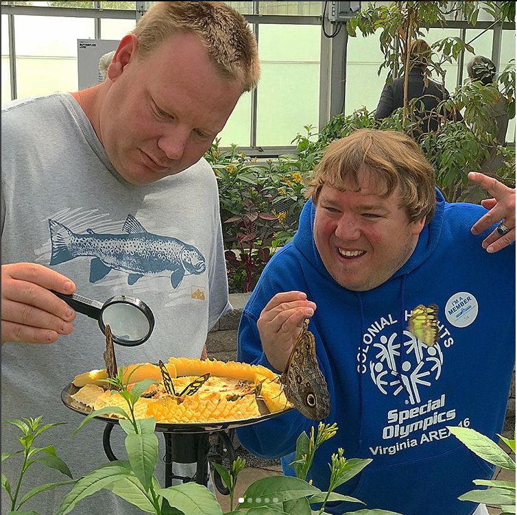Two visitors looking at butterflies in the Butterflies LIVE! exhibition at Lewis Ginter Botanical Garden
