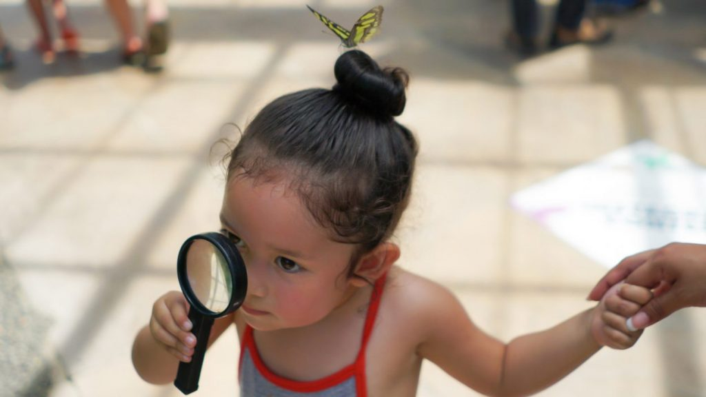 Girl looking for butterflies with magnifying glass with butterfly on her head. Image by Israel Ramirez