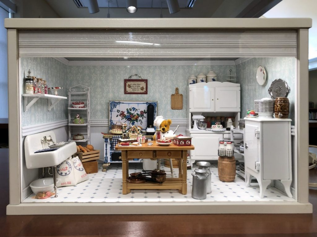 Diorama of a kitchen scene, with a teddy bear baking holiday treats