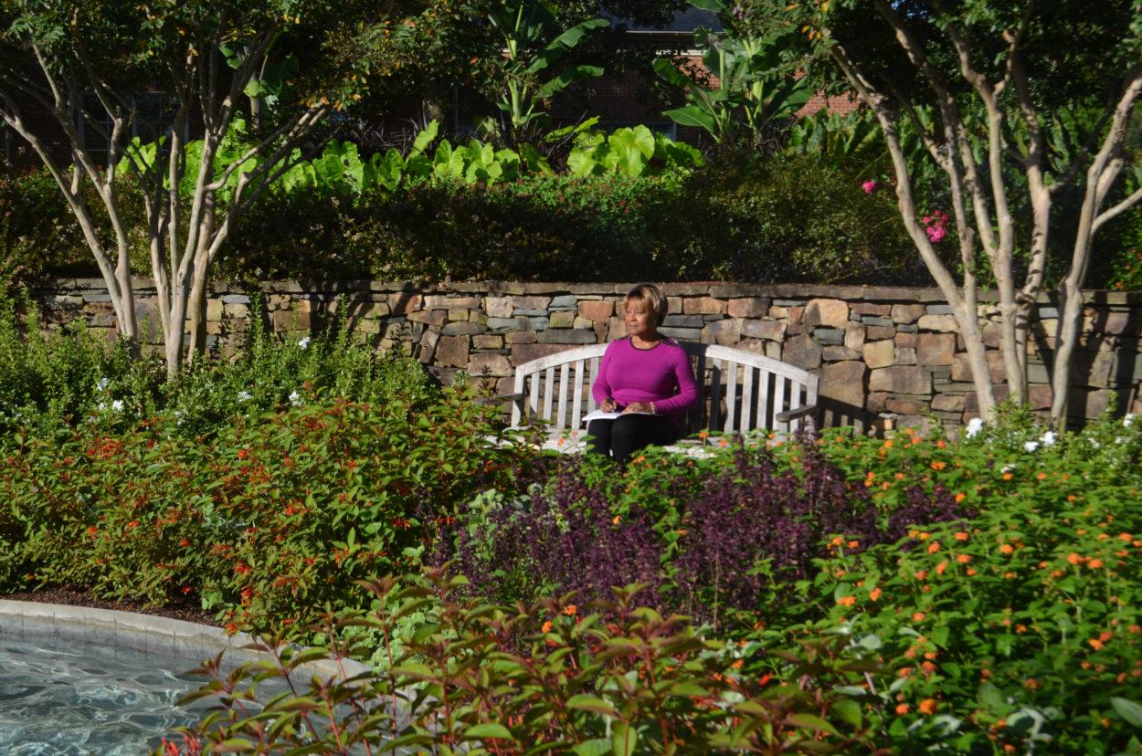 Woman sitting at Lewis Ginter Botanical Garden journaling