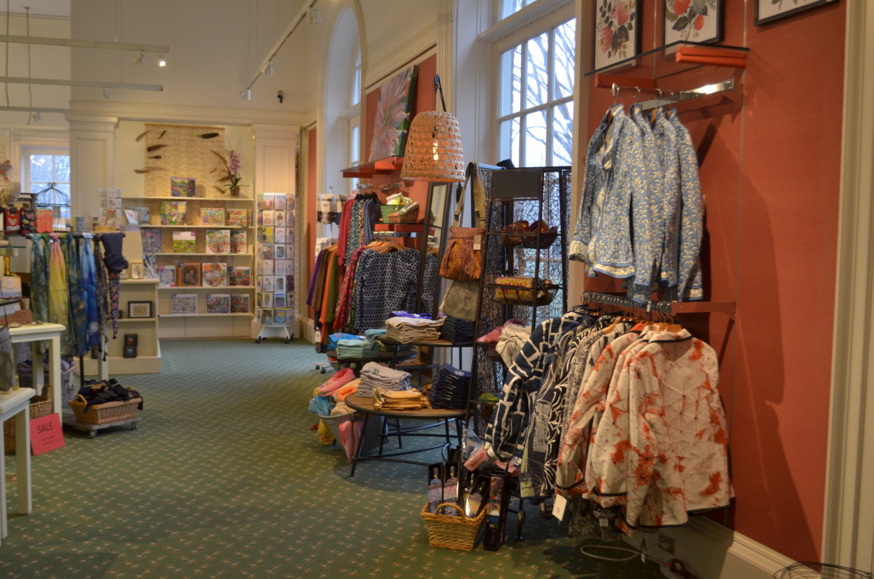 The entry of the shop showcasing a wall lined with clothing racks and tables.