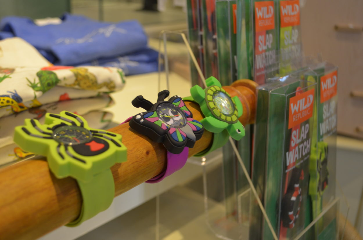 Three slap bracelets with watch faces are displayed on a wooden pole. There is a spider, butterfly and turtle,