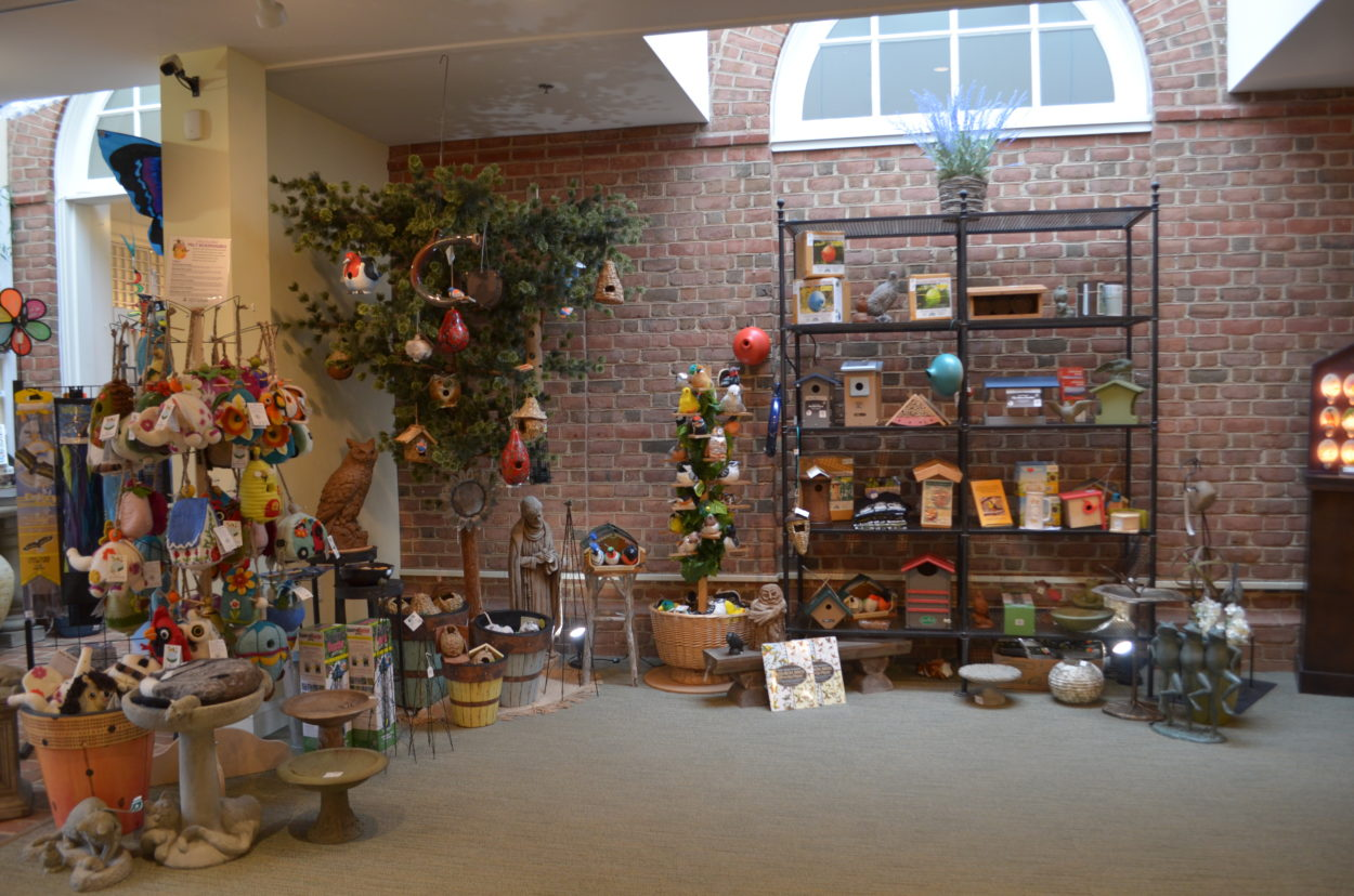 Wide shot of bird display with felted bird houses, wooden birdhouses, stuffed animals and feeders.
