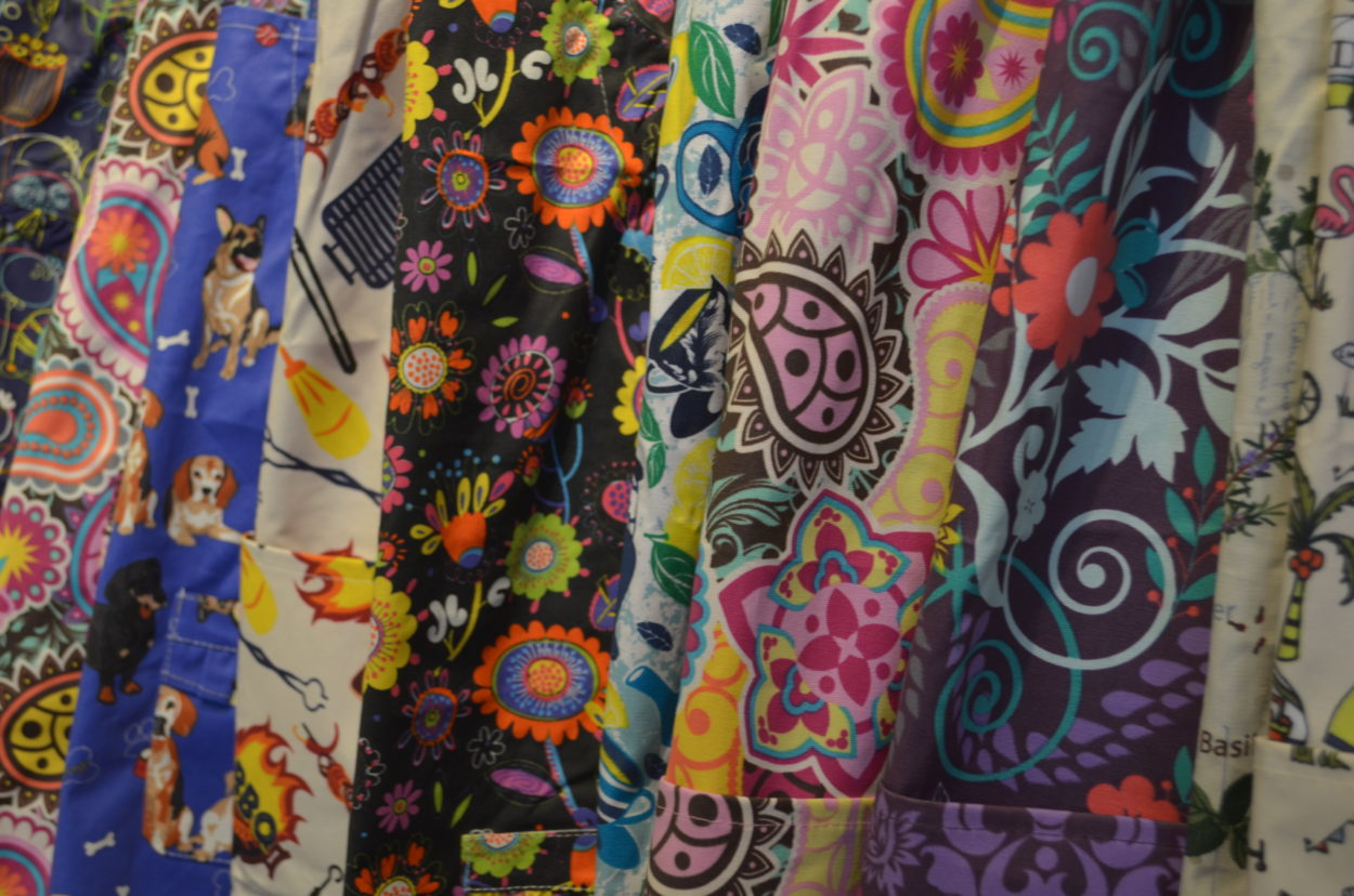 Tight shot of various apron prints ranging from dogs and barbecues to paisley and floral designs. All of them are brightly colored.