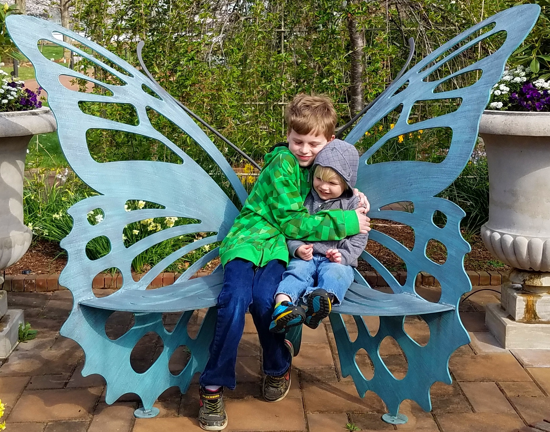 Jennifer's sons hugging on a butterfly bench and enjoying the therapeutic benefits of the Garden.