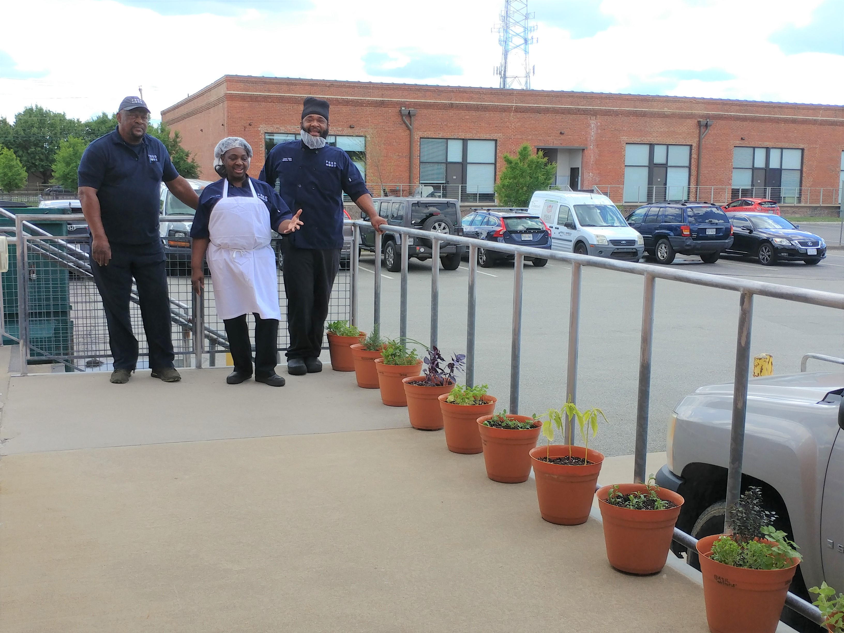 Feed More's loading dock lined with herbs in pots getting fresh sun.