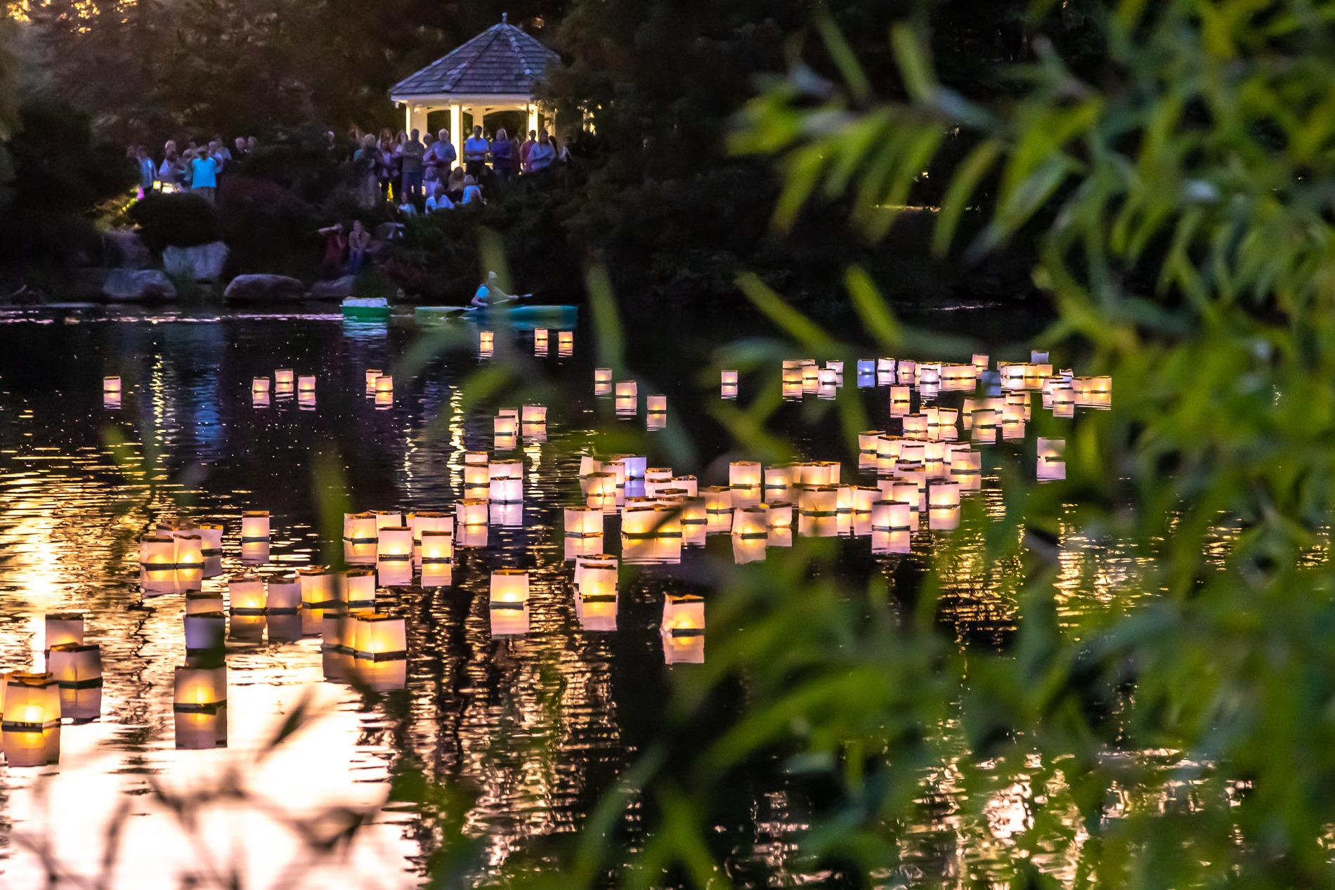 Floating lanterns at the festival showing the lake at night with votive candles. Image by Tom Hennessy