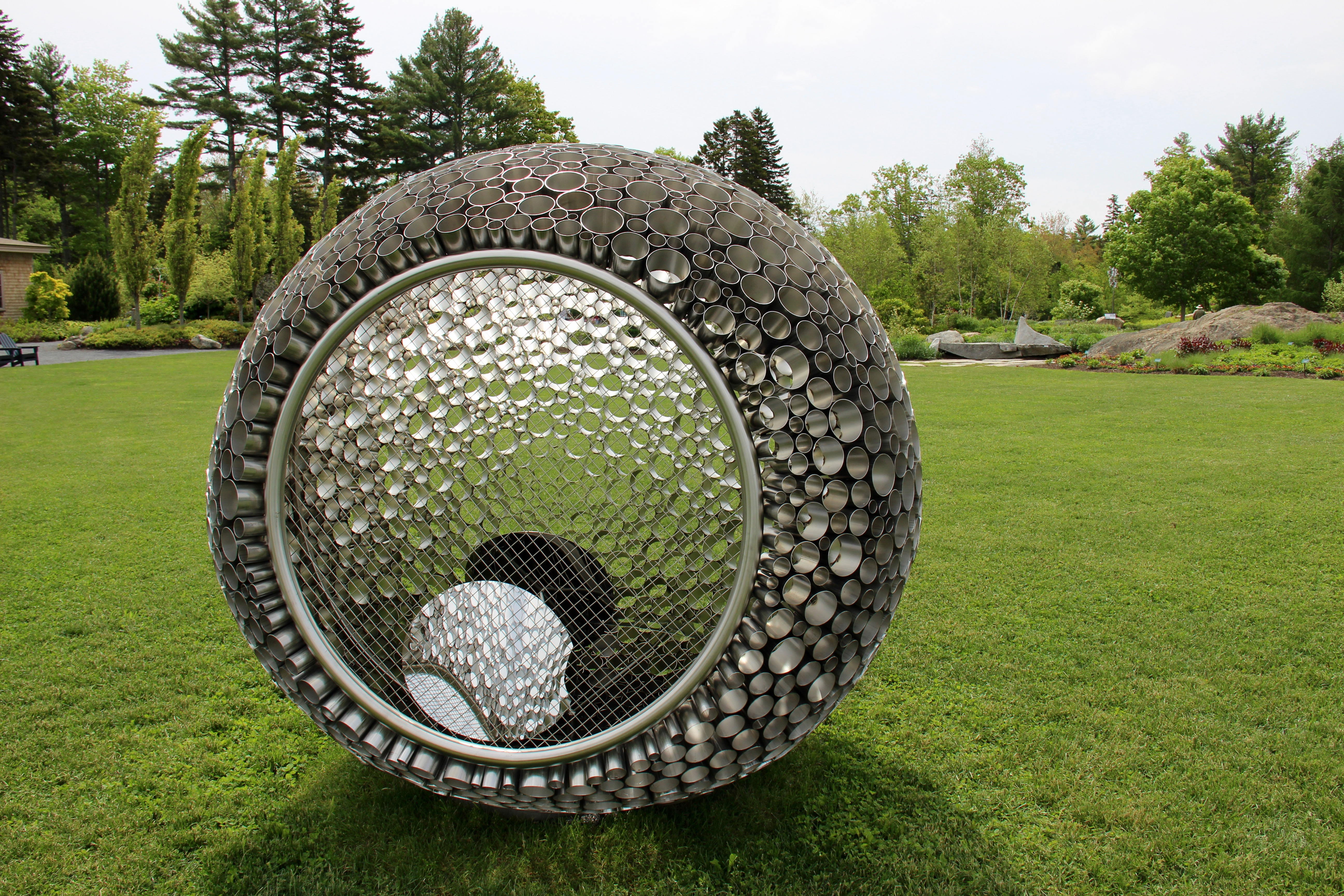 A silver orb sculpture from Wind, Waves and Light by George Sherwood