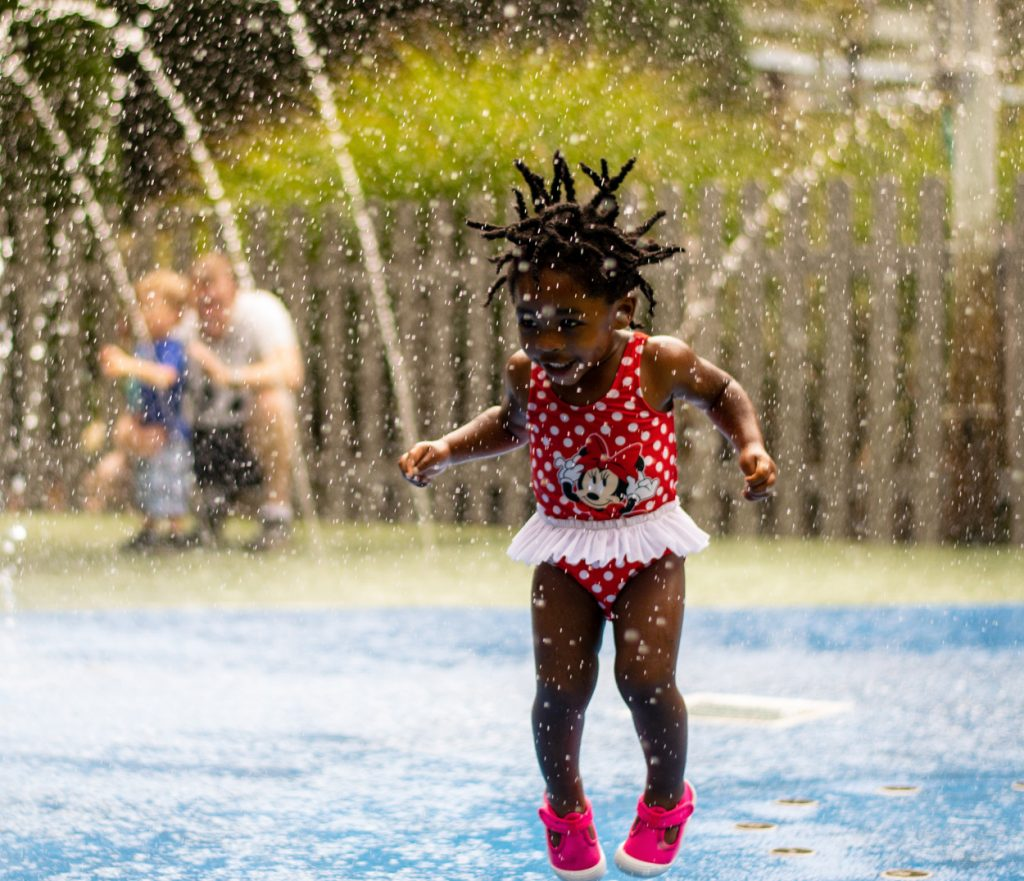 Girl jumping with hear flying in waterplay at Lewis Ginter