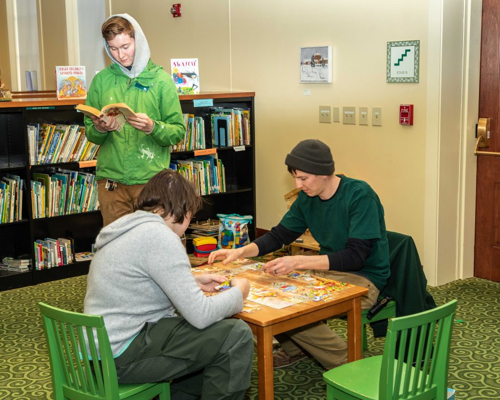 Two adults play with a puzzle at a child-size table in the Library; a third stands behind them reading a children's book