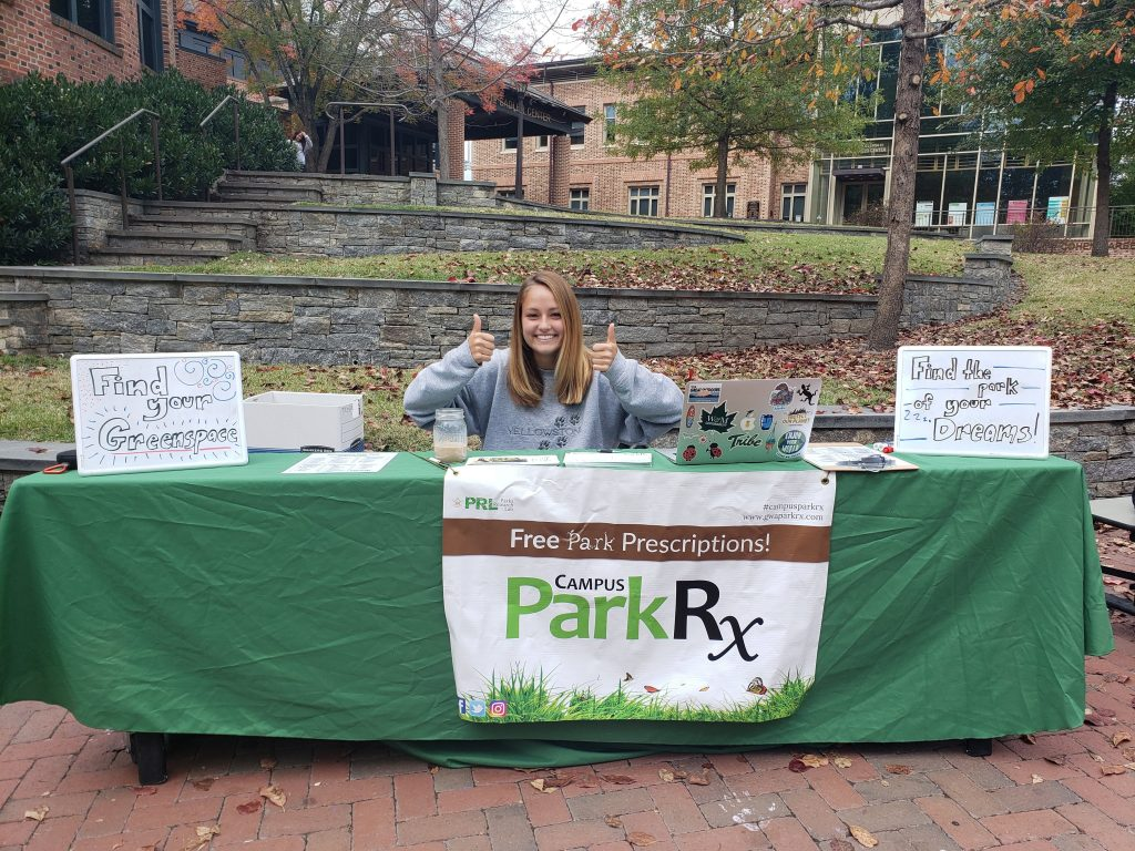 Woman tabling at the College of William & Mary for students to get outdoors more for outdoor recreation.