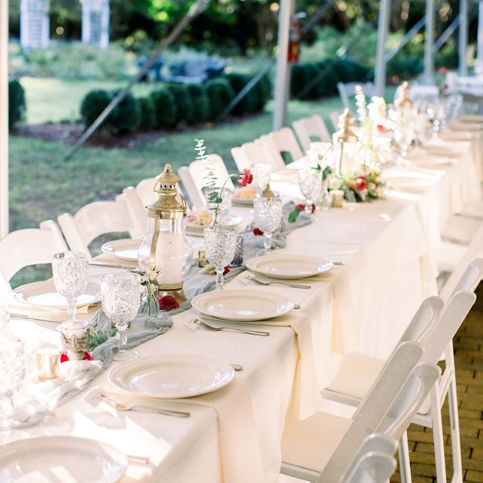 A long dinner table covered with simple glassware, lanterns and a few flowers to add color.