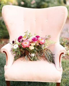 Light pink vintage love seat with a bouquet of flowers sitting on top.