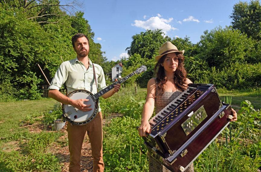 man with banjo and woman with harmonium standing at farm