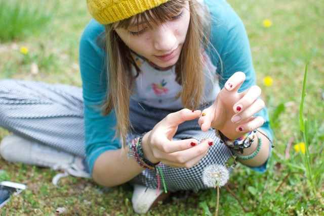 Girl examining a dandelion as part of a citizen science project in her backyard. Image by Mitra Bryant