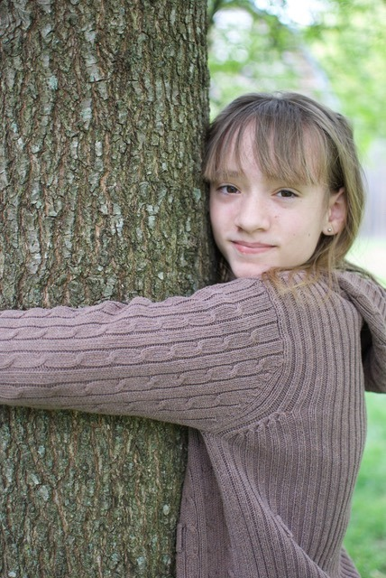 Girl hugging tree. The value of trees is substantial. Especially, if you have a favorite memory or personal connection to a tree. Image by Mitra Bryant