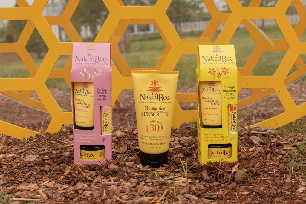 product display of gift sets that include hand lotion, body butter, and lip balm, and sunscreen on mulch in front a honeycomb pattern