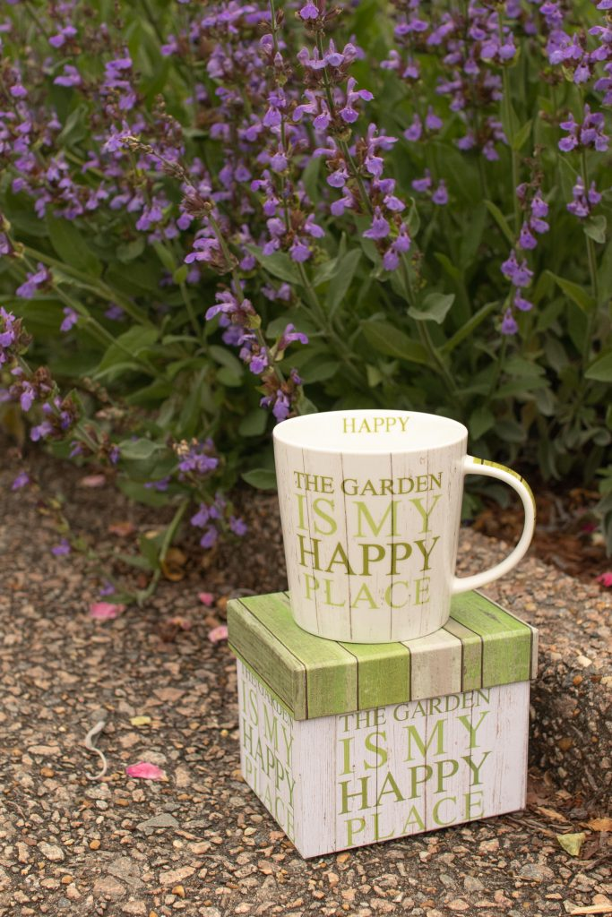 "mug with green, stacked, uppercase text on the outside that reads, ""the garden is my happy place"" there is also text on the inside of cup at the lip that reads ""happy"" the mug is on top of a box that also says ""the garden is my happy place"""
