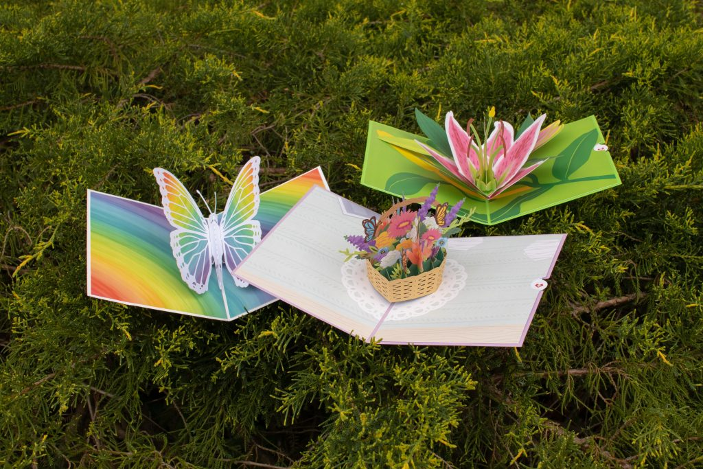 three 3-D pop-up paper cards, one of a rainbow butterfly, one of a woven basket of flowers and one of a lily