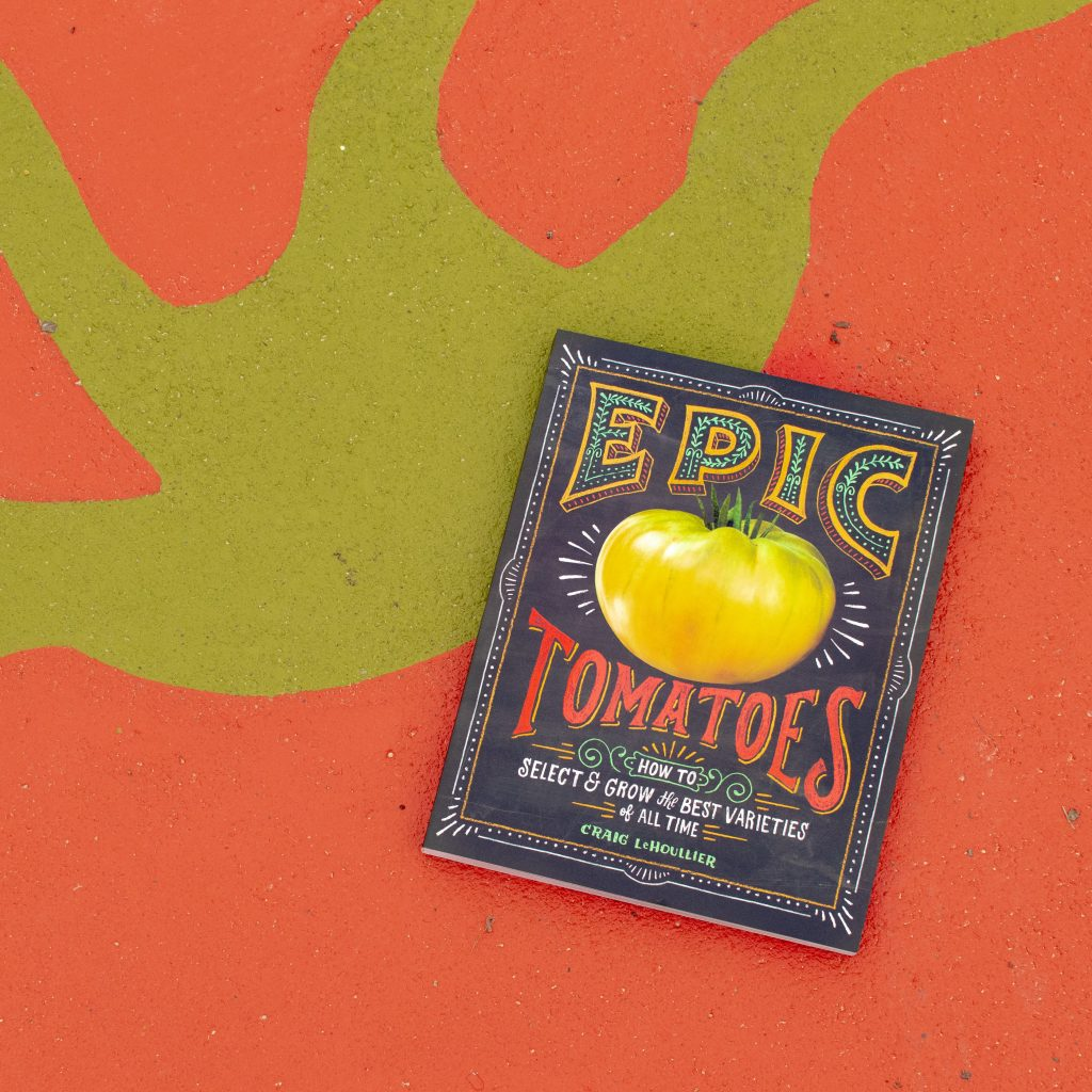 "black book with a large yellow tomato on the front and ""Epic Tomatoes"" in large text on top of a red and green tomato mural on concrete"