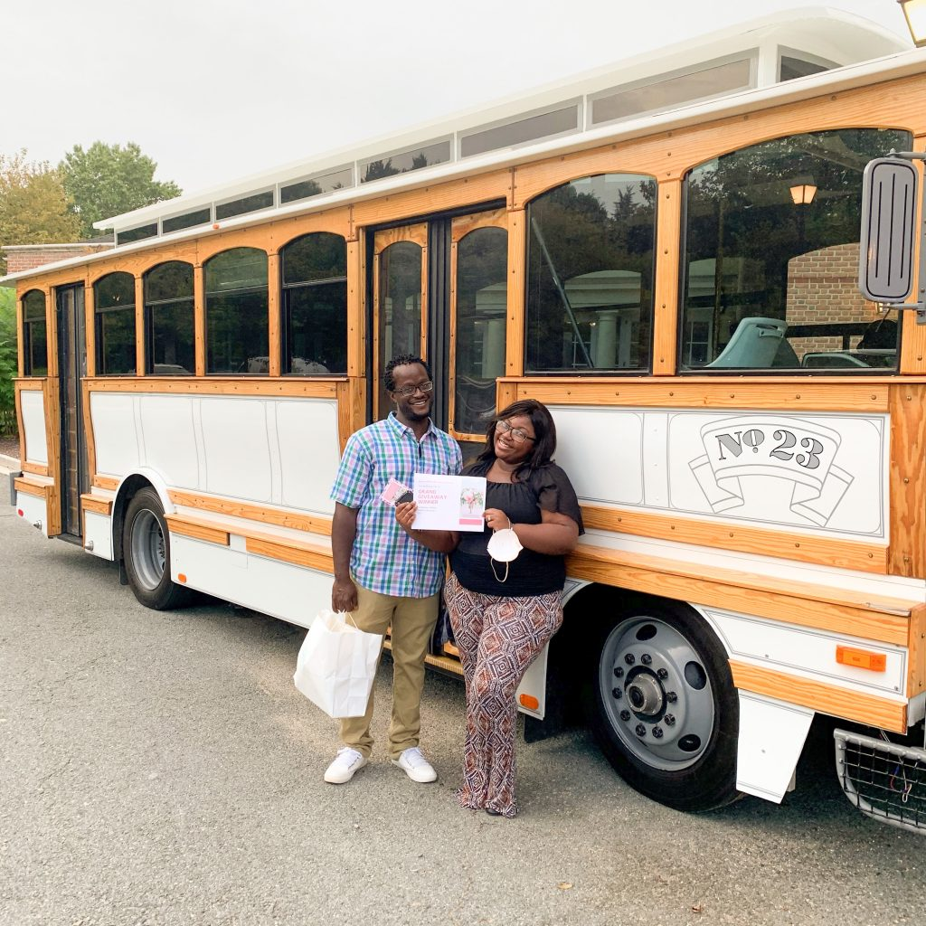 Grand Giveaway winning couple posing in front of the RVA on Wheels trolley