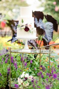 white wedding cake display from Louisa's Homemadeson a brass cart amongst flowers