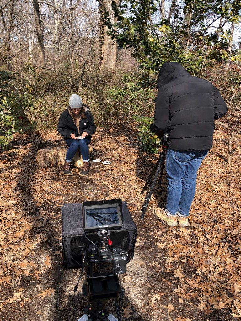 Mitra Bryant sits on a tree stump outside to look at her notes before being filmed for a virtual field trip video.