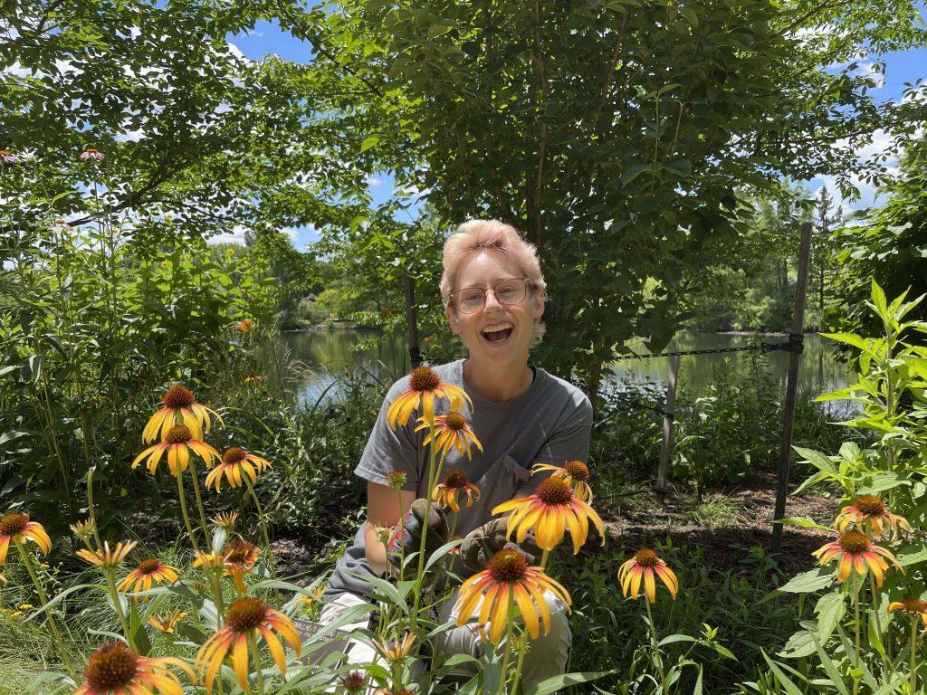 New seasonal gardener Jaimie Woll posing behind plants.
