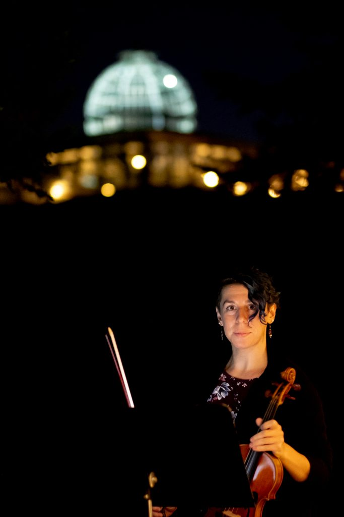 Violinist Becca Longhenry in the dark with just a small amount of light and the Conservatory in the background. Image by Harlow Chandler